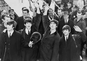 John Lennon (l.) as The Beatles invade America in 1964